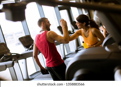 Young woman and personal male trainer rest in the gym after workout