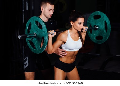 Young woman and personal trainer exercise in gym. Fitness, sport, exercising and diet concept. Barbell training.