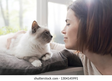 Young woman petting her beautiful cat at home next to a window, pets and lifestyle concept