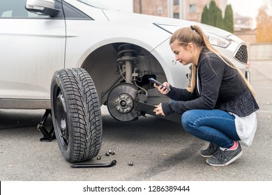 Young woman phoning near car without wheel
