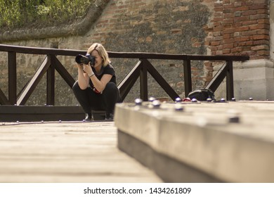 Young woman photographer with backpack taking pictures with SLR camera, capture old town beauty