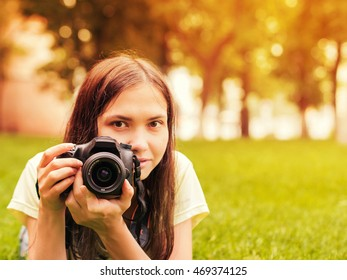 Young woman photographer with camera lie down on grass. Image with copyspace and sunkissed effect. Focus at camera. Shallow DOF