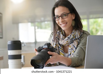 Young woman photographer checking previews on camera
