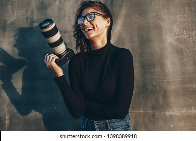 Young woman photographer with her professional camera smiling against oliphant backdrops. Woman photographer with digital camera.