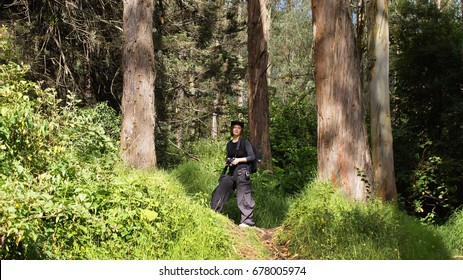 Young woman, photographer on path in Cloud Forest on highlands near Peguche waterfall, Otavalo, Ecuador