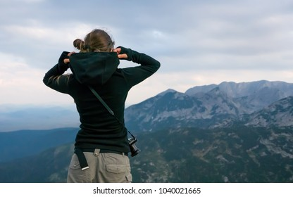 Young woman photographer preparing for a storm at the top of the mountain