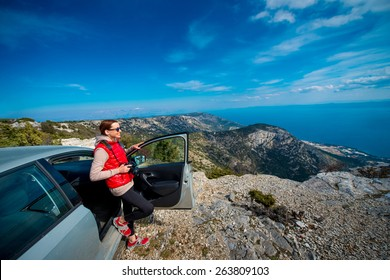 Young woman photographer standing near her car on the top of mountain