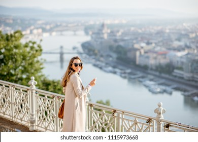 Young woman photographing beautiful morning view on Budapest city from the Gellert hill in Hungary