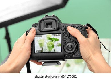 Young woman photographing juice in photo studio, closeup
