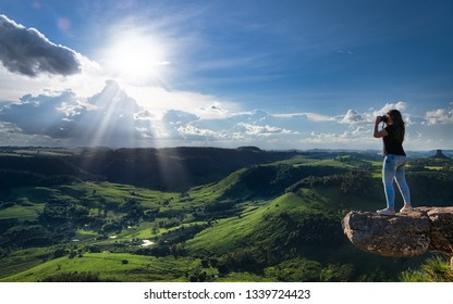 Young woman photographing the landscape at sunset from the Morro do Gavião, Ribeirão Claro, Parana State, Brazil