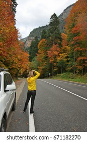 Young woman photographing on asphalt road in colorful autumn forest against mountains.