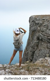 Young woman photographing on top of mountain against sea at cloudy weather. Back view.
