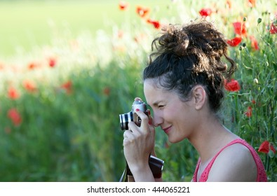 Young woman photographing with a poppy field