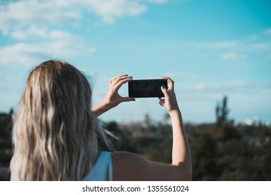young woman photographing with smartphone
