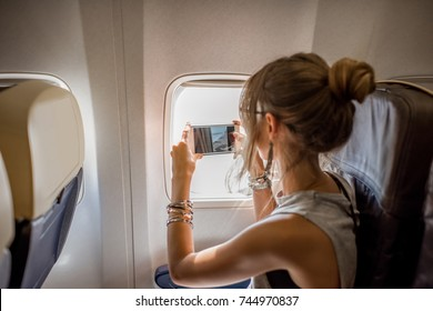Young woman photographing view from the aircraft window during the flight in the airplane