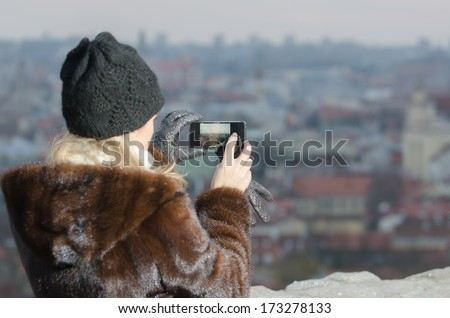 Young  woman photographing winter cityscape of Vilnius, capital city of Lithuania.  Vilnius Old Town is one of the largest  medieval old towns in Eastern Europe.