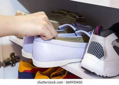 Young woman picking court shoes in the cabinet