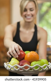 A young woman is picking up a piece of fruit, smiling, and looking away from the camera.  Vertically framed shot.