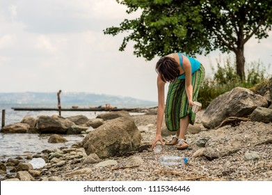 Young woman picking up the plastic bottle garbage, cleaning on the coastal strip. Volunteer concept.