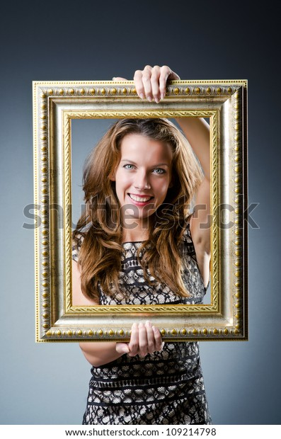 Young woman with picture frame on white
