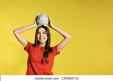 Young woman with piggy bank on color background, space for text. Money saving