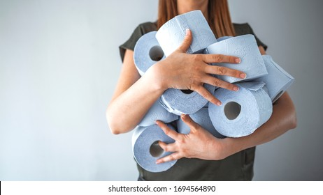 Young woman with a pile of toilet paper holds out one roll during Coronavirus outbreak or Covid-19. Buying panic due to coronavirus covid-19, people buy essentials in bulk in supermarkets concept.