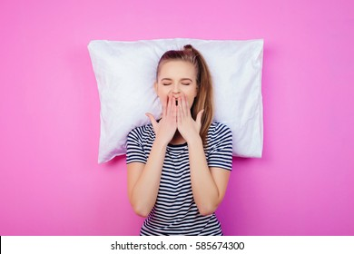the young woman with a pillow on the pink wall