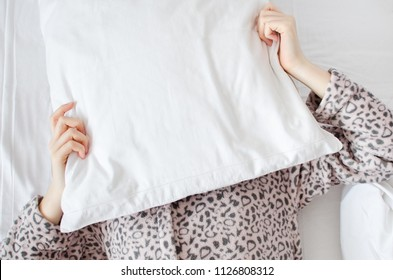Young woman with pillow over her head in the morning. Student or schoolgirl do not want to wake up early for school or univercity. Oversleep, not getting enough sleep concept. Top view. Copy space.
