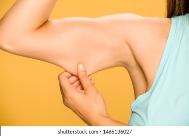 Young woman pinching fat on her hand on yellow background