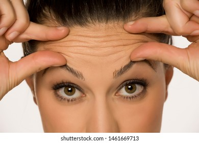 young woman pinching her forehead wrinkles with her fingers on a white background