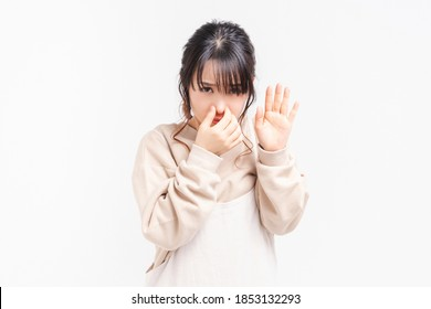A young woman pinching her nose taken in the studio