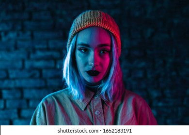 Young woman in pink and blue neon light. Portrait of unusual beautiful punk girl with colorful hairstyle on bricks wall studio background