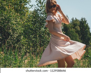 Young woman in a pink dress is spinning around herself at the edge of the forest. Copy space.