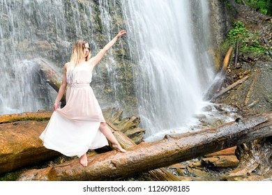 Young woman in pink dress stands barefoot on log, her arms are raised and doing some dreamlike movement and expressing happy feeling at the Bridal Veil Falls Provincial Park in Chilliwack, B.C. Canada