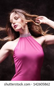 young woman in pink elegant dress in motion studio shot