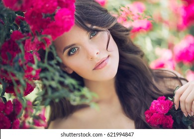 Young woman with a pink flower. Outdoor summer shot