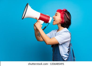Young woman with pink hair over blue wall shouting through a megaphone