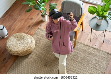 Young woman pink hair wears vr headset goggles holds controllers plays vr video game futuristic immersive simulator explores virtual reality 3d 360 cyber game experience at home looking up, top view.