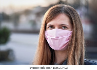 Young woman with pink hand made cotton face nose mouth mask portrait, blurred empty city behind her. Can be used during coronavirus covid-19 outbreak prevention