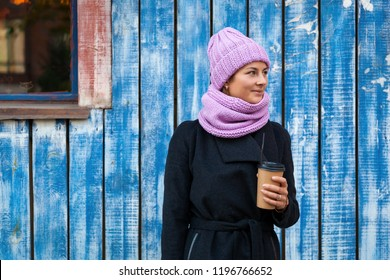 A young woman in a pink knitted hat, black coat and backpack  enjoys city, poses and drink coffee to go around blue wall. The concept of livestyle and outdoor recreation in autumn