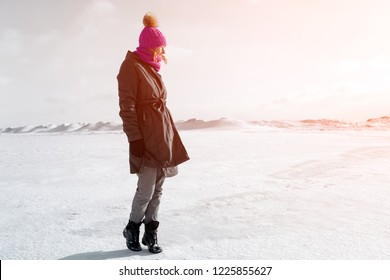 A young woman in a pink knitting hat,  black coat  enjoys winter nature, walking on the frozen sea at the north pole around blue sky in winter . The concept of livestyle and outdoor recreation