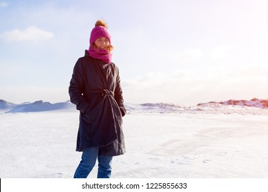 A young woman in a pink knitting hat,  black coat  enjoys winter nature, walking on the frozen sea at the north pole around blue sky. The concept of livestyle and outdoor recreation in winter