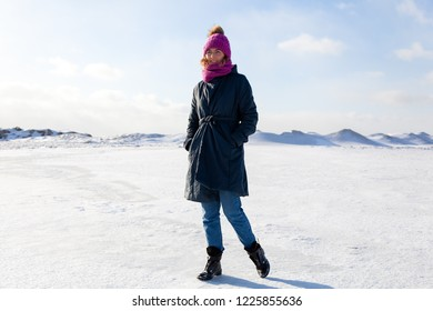 A young woman in a pink knitting hat,  black coat  enjoys winter nature, walking on the frozen sea at the north pole around blue sky in winter frosty day. The concept of livestyle