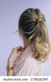 young woman in a pink lapel collar short sleeve shirt with a messy twisted balayage ponytail and golden accessories back view photo
