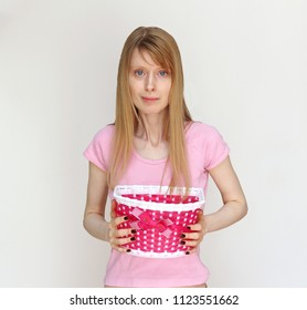 Young woman in pink shirt holding basket with decorative bow