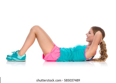 Young woman in pink shorts and turquoise shirt lying down on a floor and doing crunches exercise. Side view. Full length studio shot isolated on white.