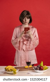 Young woman in a pink silk robe stands near a table with fruits and poses on a red background