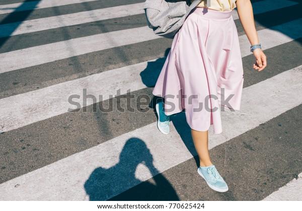 ピンクのスカートをはいた若い女性と、夏に道路を横切るスニーカー