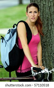 Young woman in pink tanktop standing next to bicycle in park holding backpack