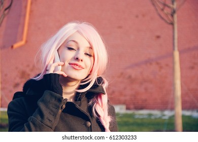 Young woman in the pink wig talking on mobile phone on the street